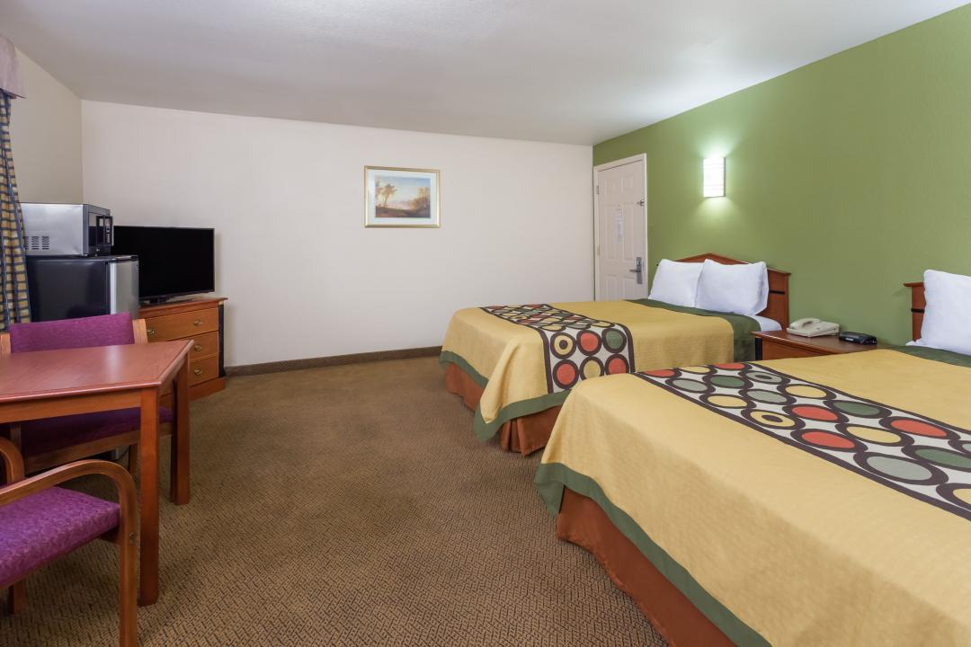 Guestroom with two queen beds, flatscreen TV, sofa, refrigerator, microwave and dining area for two