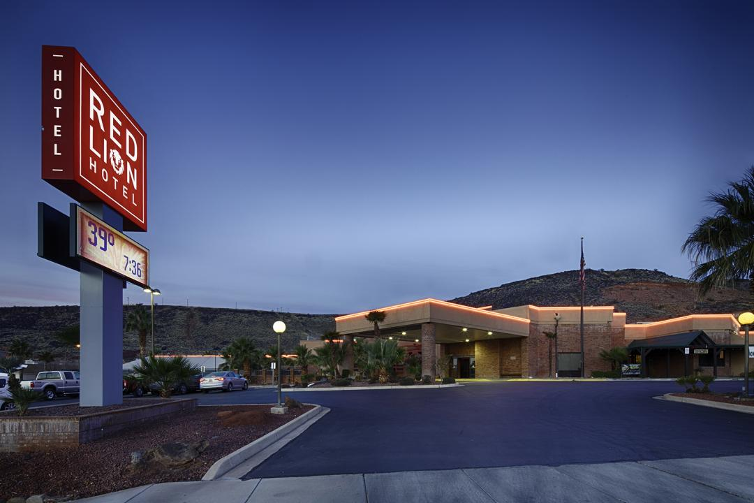 Lit up exterior with sign and hills in the background at dusk