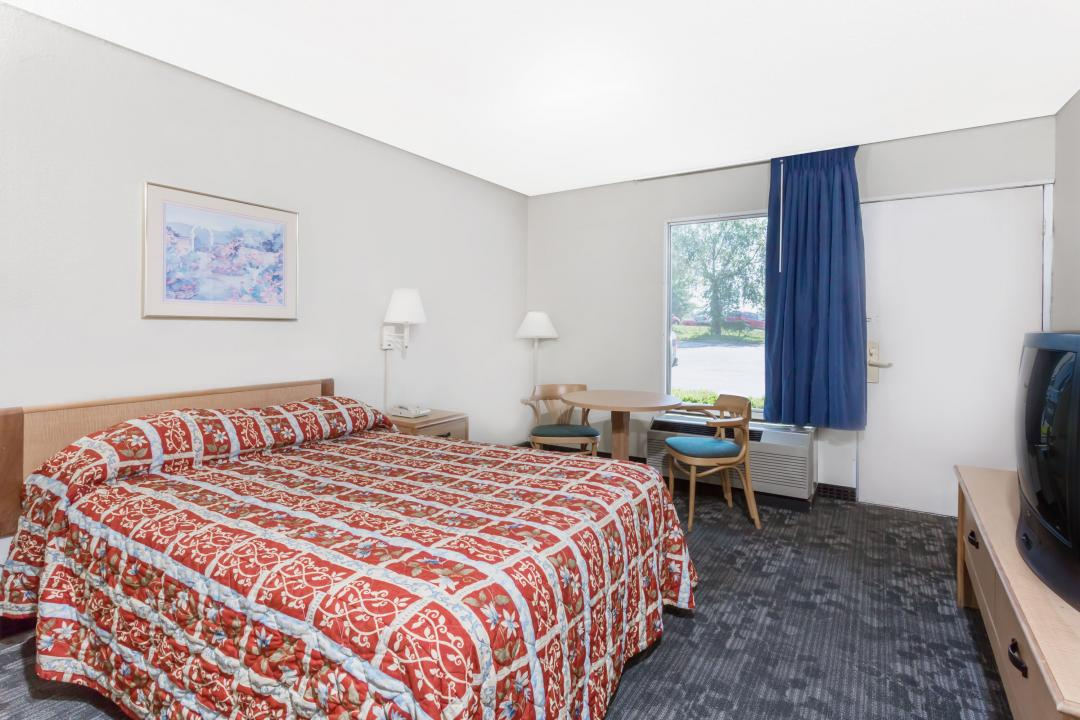 Guest room with one queen bed, table and chairs