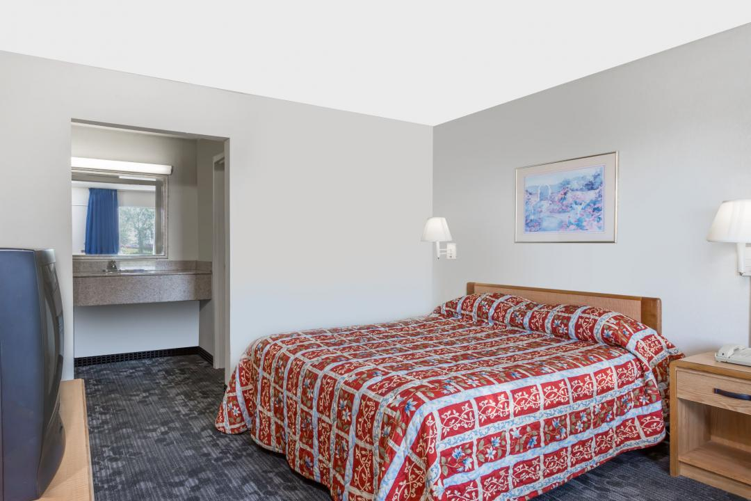 Guest room with one queen bed and a nightstand