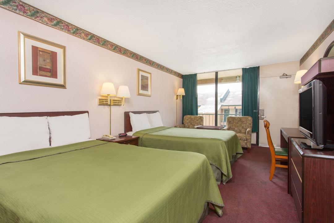 Bright two double beds guest room with armchairs, table, desk, chair and flatscreen TV.