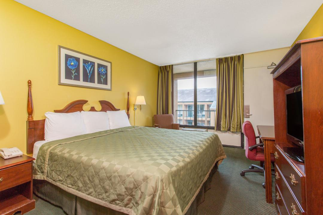 Spacious king guest room with armchair, desk, chair and flat screen TV.
