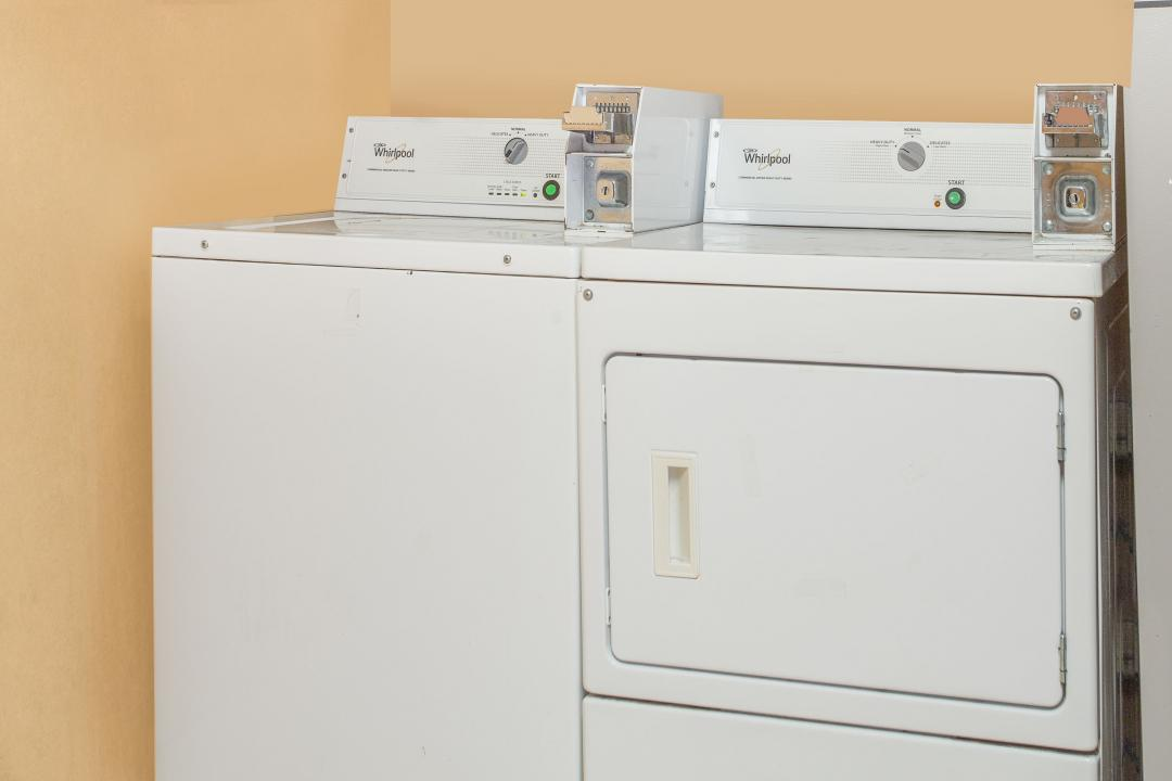 Well lit laundry room featuring washer and dryer for guest's convenience.