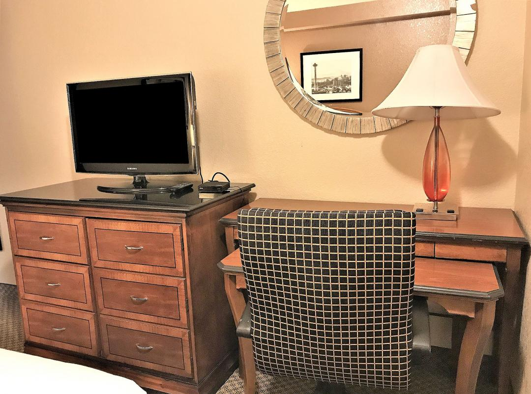 Guestroom desk with chair, round wall mirror, TV, and dresser