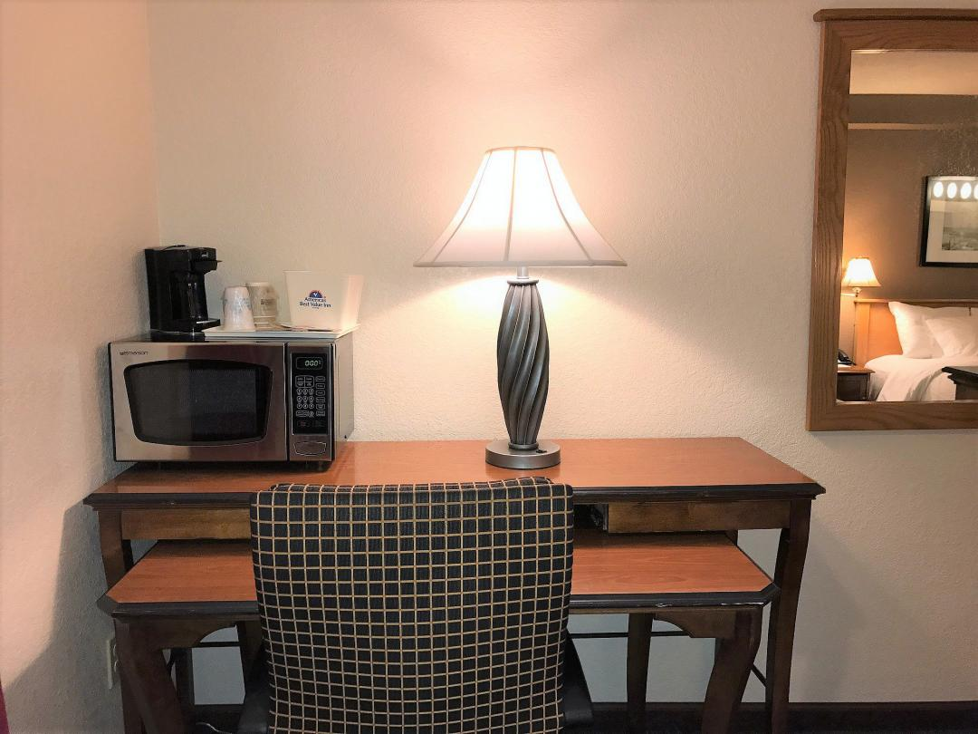 In-room desk with chair, microwave, coffeemaker, and lamp