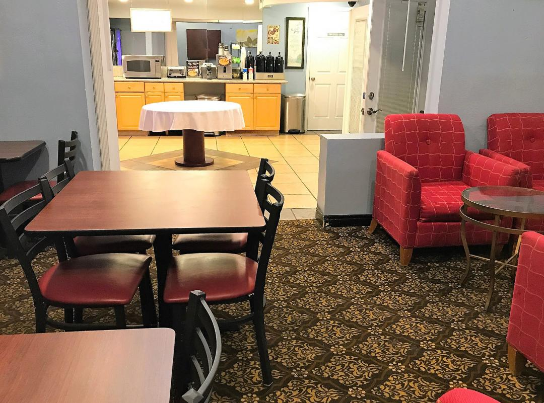 Dining area with tables and chairs, with red chairs and couch