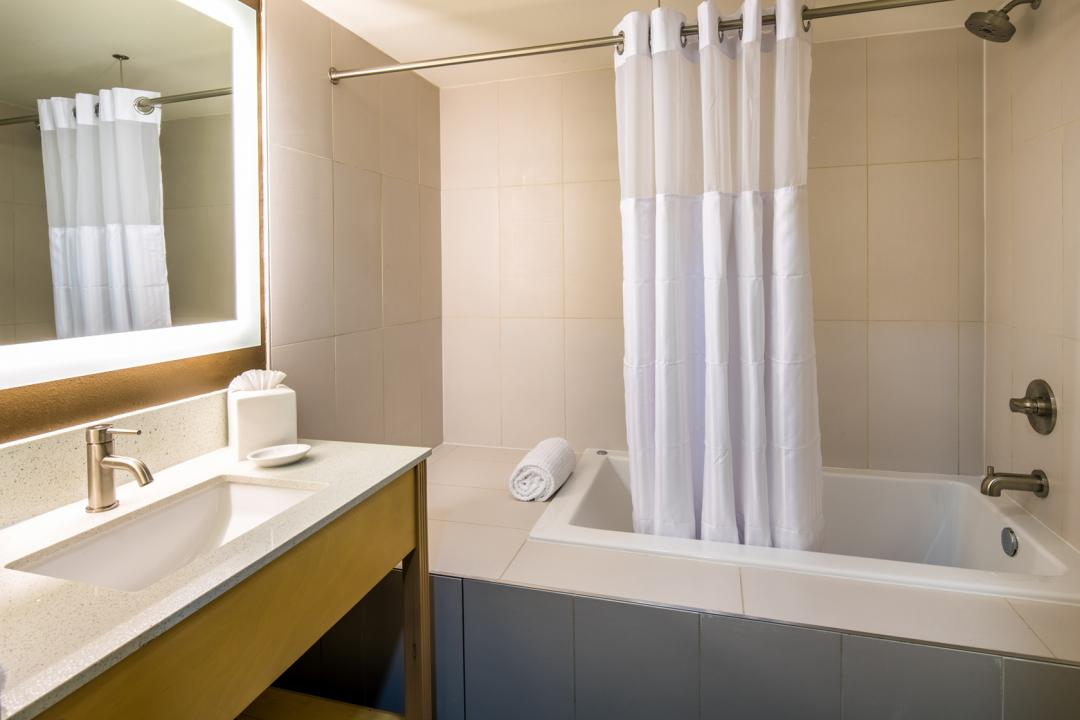 Clean, modern and well lit guestroom bathroom with step in shower