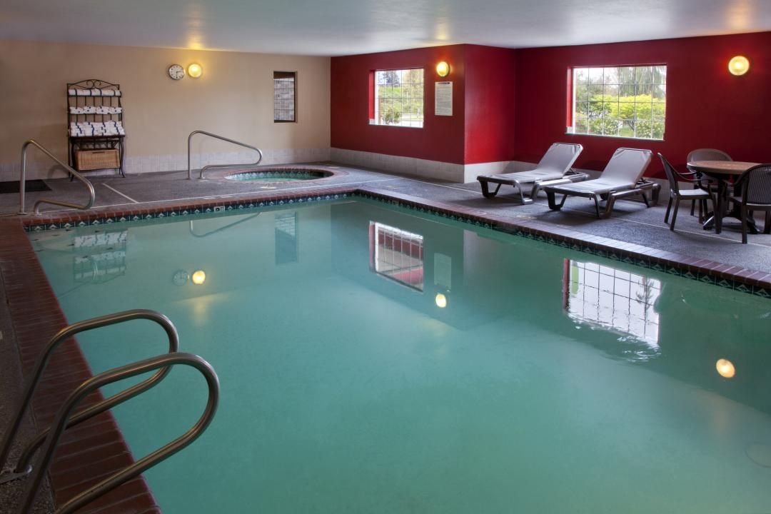 Indoor pool area with lounge chairs and Jacuzzi tub