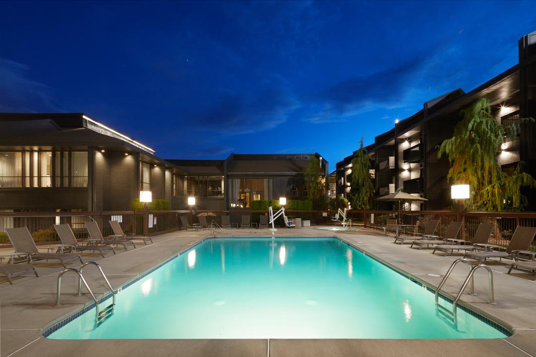 Outdoor pool area by night with lights and lounge chairs