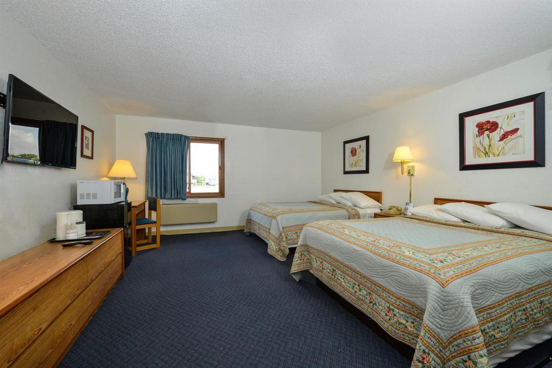 Comfortable guest room with two queen beds desk and chair