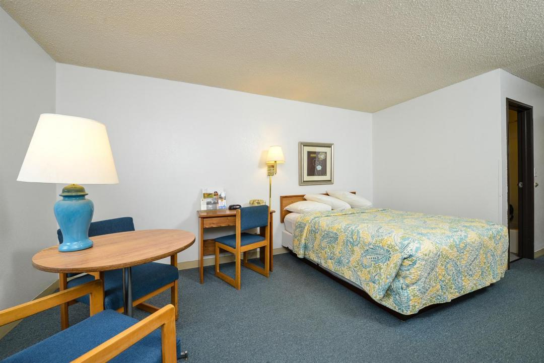 Guest room with bed, table, and two chairs