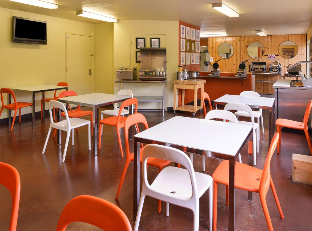 Breakfast dining area with ample dining tables, TV, buffet
