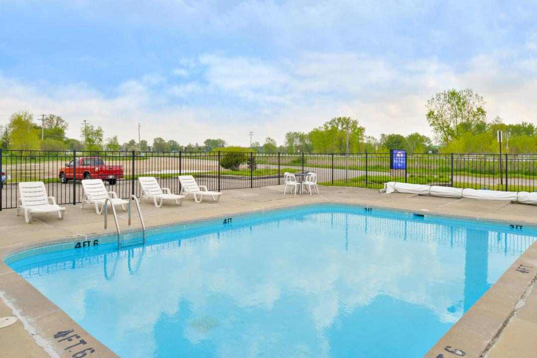 Outdoor pool and white lounge chairs by parking lot