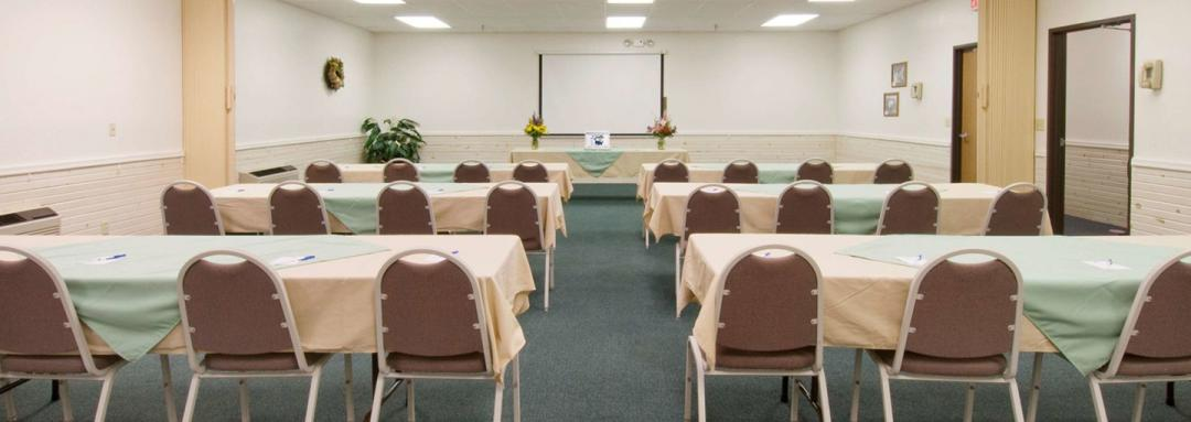 Conference meeting room with tables and chairs facing front projection screen